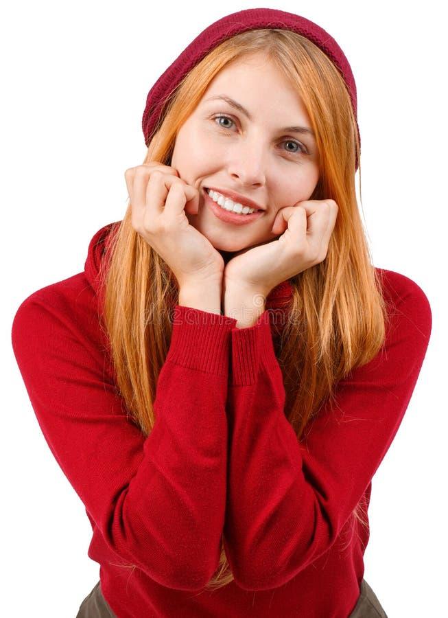 Een roodharig meisje in rode kleren houdt haar indient vuisten bij haar gezicht en zoet het glimlachen Geïsoleerde stock foto's