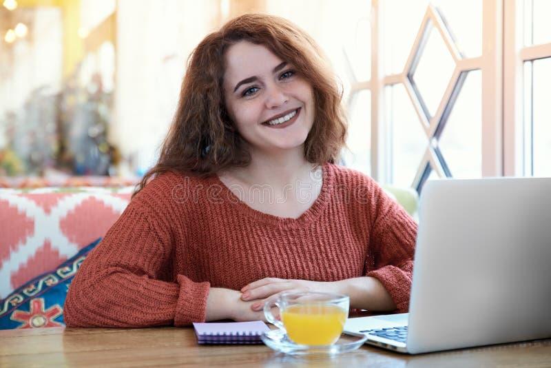 Een roodharige jonge het glimlachen zitting van het studentenmeisje in een Zonnige koffie stock fotografie