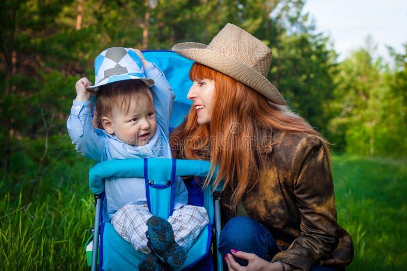 Een roodharige vijftig-jaar-oude glimlachende vrouw in een hoed en een twee-jaar-oude jongen in de zomer in het hout royalty-vrije stock foto's