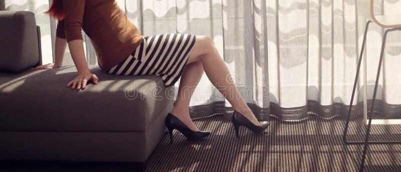 Een roodharige vrouw in korte gestreepte rok wacht uitgestrekt op een bank in een zonnige hotelruimte met hoge hielen en naakte b stock fotografie
