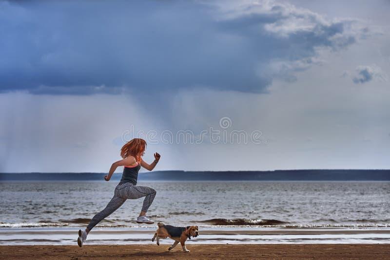 Een roodharige vrouw op middelbare leeftijd in sportkledingslooppas langs de zandige kust van een grote rivier met haar puppy stock foto