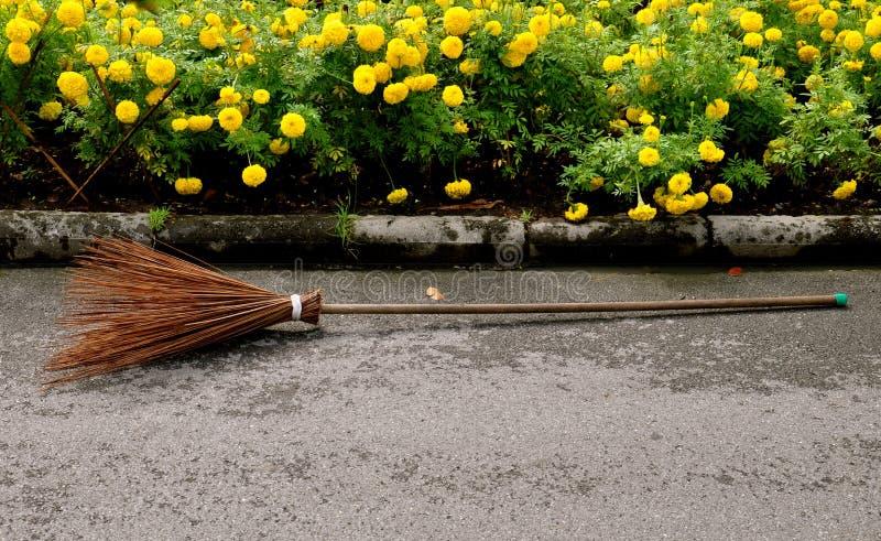 Een rotanbezem voor een massa van gele goudsbloem bloeit stock fotografie