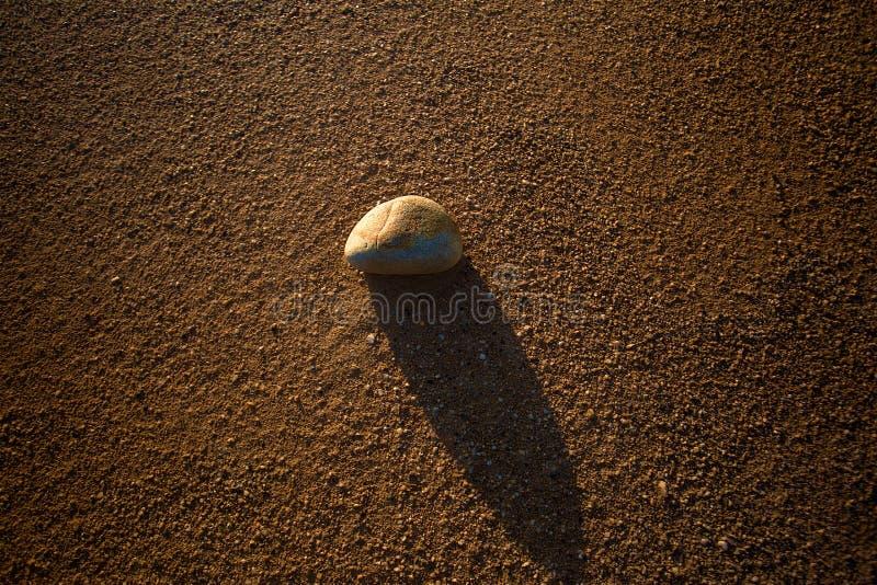 Een rots en zijn schaduw over het zand in een woestijn stock fotografie