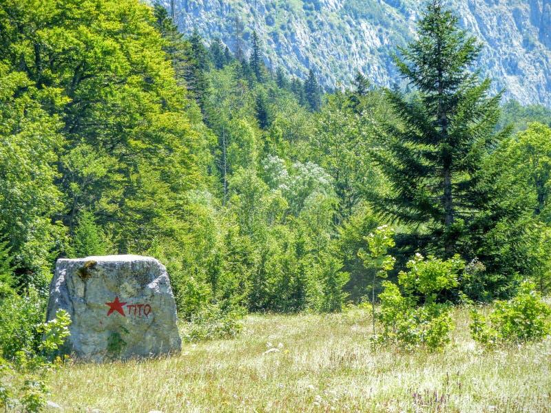 Een rots met een rode inschrijving van de naam van een dictator van het voormalig Joegoslavië in de bergen van Montenegro royalty-vrije stock afbeelding