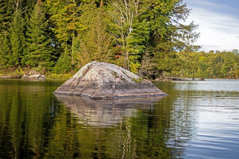 Een rots staat garant voor een klein, bebost eiland royalty-vrije stock fotografie
