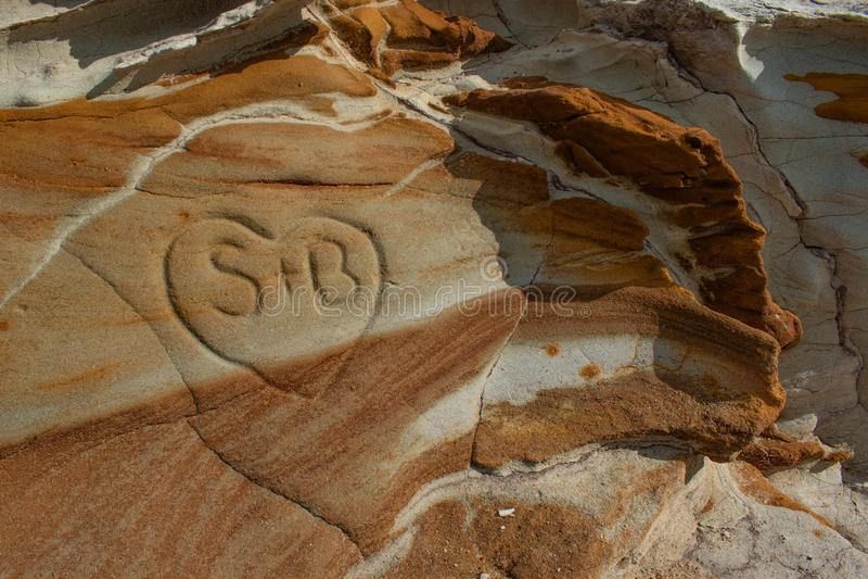 Een rotsdagzomende aardlaag met interessante patronen en kleuren en een hart sneden in de rots royalty-vrije stock afbeelding
