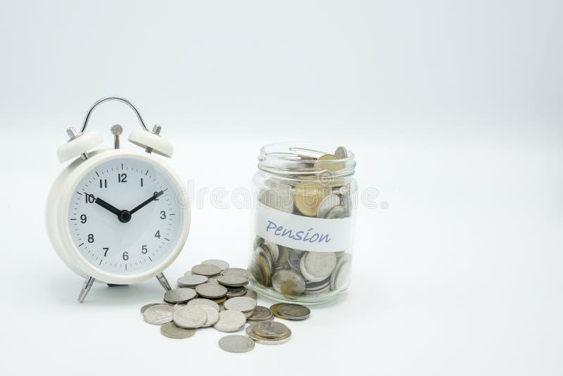 Een roze die spaarvarken naast een glasfles met muntstukken geëtiketteerd wordt gevuld pensioen en wit alarm watc stock afbeelding