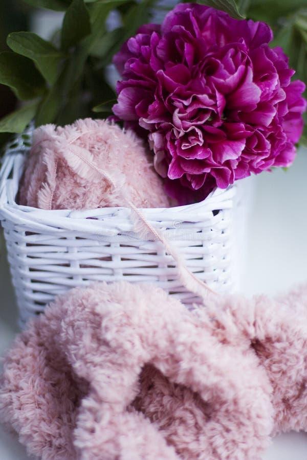 Een roze gebreid stuk met pluizig garen en een pioen royalty-vrije stock fotografie
