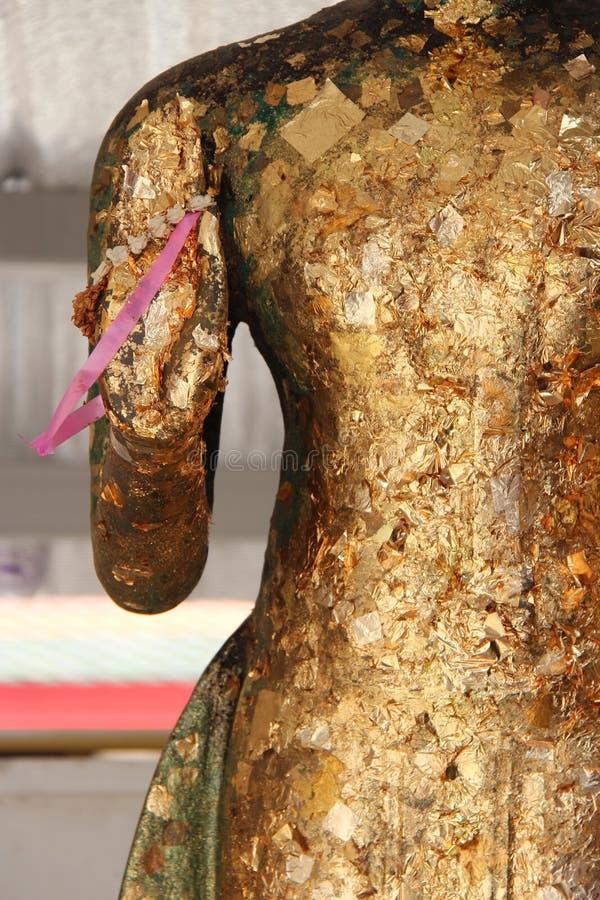 Een roze lint wordt vastgehaakt aan de hand van een standbeeld van Boedha (Thailand) stock foto