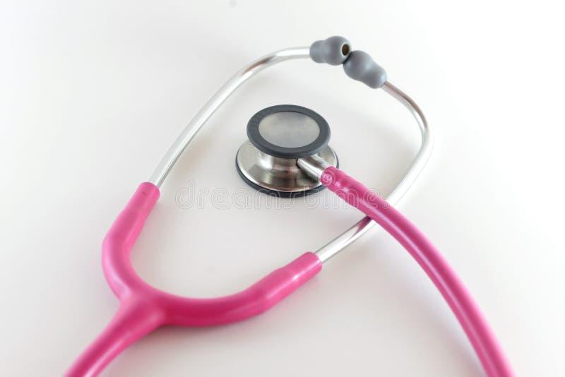 Een roze stethoscoop wordt gezien op een witte achtergrond royalty-vrije stock foto