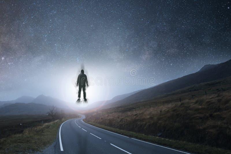 Een rubriek van de bergweg in de afstand bij nacht met sterren in de hemel met het silhouet van een mens die in de hemel, met a d stock fotografie