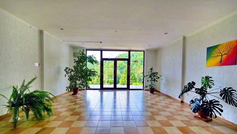 Een ruime zaal met een balkon, multi-colored tegels op de vloer en sierplanten stock afbeelding