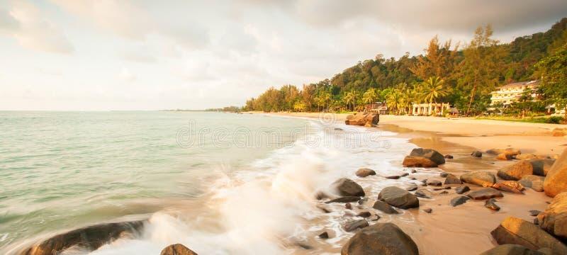 Een rustig tropisch zeegezicht op de zomerschemer, zachte golven en mooie kiezelstenen op het gouden strand stock foto