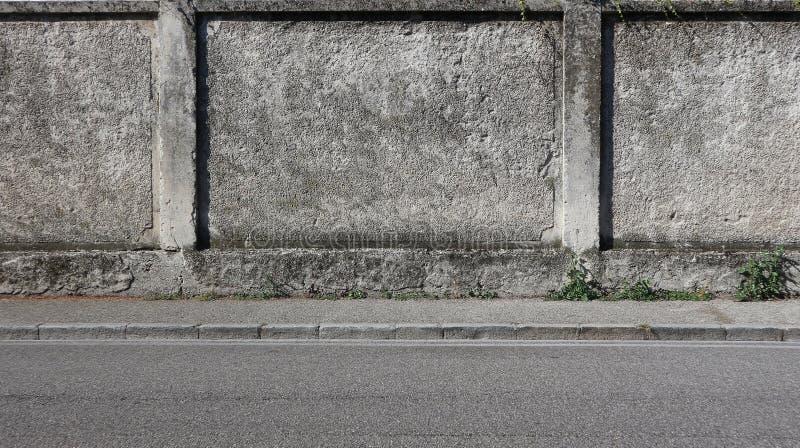 Een ruwe concrete muur met een grijze stoep en een asfaltweg Stedelijke achtergrond voor exemplaarruimte stock afbeeldingen