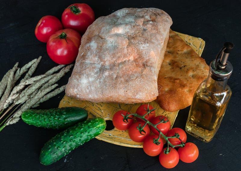 Een samenstelling van groenten en brood in een rustieke stijl op een zwarte houten lijst De komkommer van broodtomaten royalty-vrije stock foto's