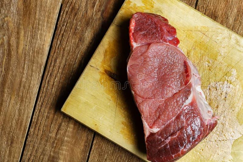 Een sappig bloedig rundvleeslapje vlees ligt op een houten Hakbord royalty-vrije stock foto's