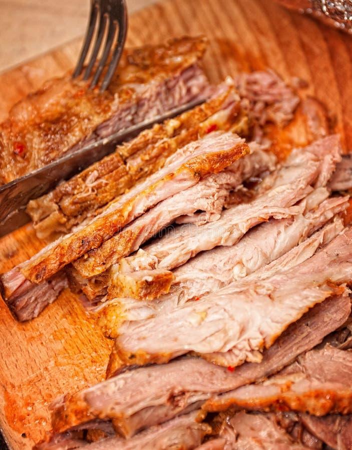 Een sappig vers gebakken varkensvlees met kruiden en kruid op houten scherpe raad royalty-vrije stock afbeeldingen