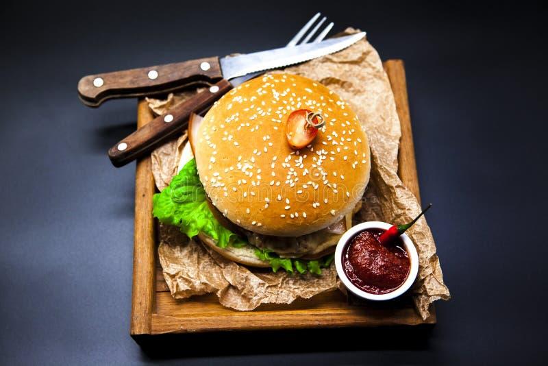 Een sappige Hamburger Hamburger met marmeren rundvlees, vork met mes en Spaanse pepersaus op de krant royalty-vrije stock afbeelding