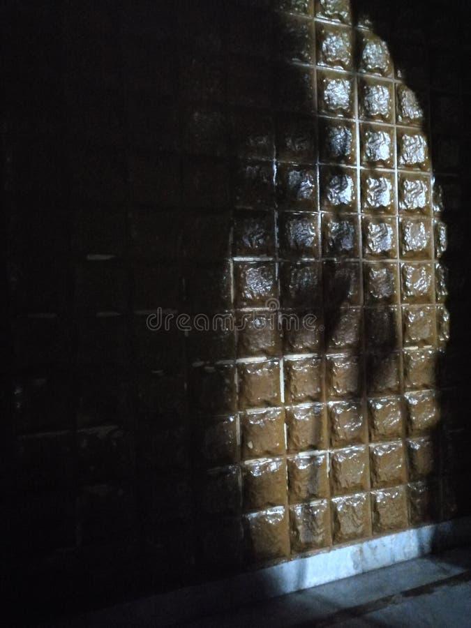 Een schaduw van een boom en een overspannen deur op de muur in de straatlantaarn stock foto's