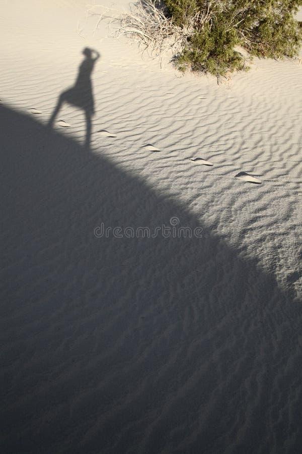 Een schaduw van een meisje die zich op wit zand bevinden royalty-vrije stock afbeelding