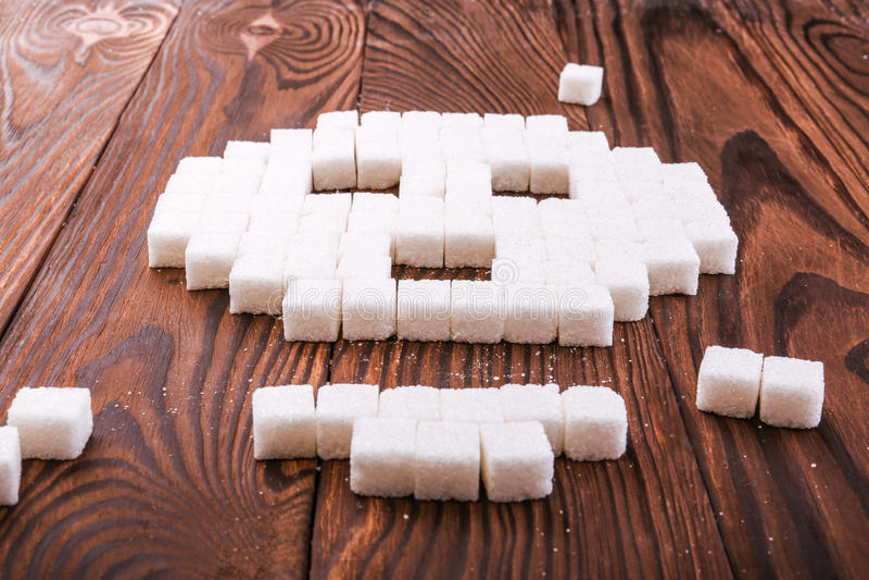 Een schedelsymbool van suikerkubussen die wordt gemaakt Stukken van suiker op een houten achtergrond Het concept van de suikerver stock foto