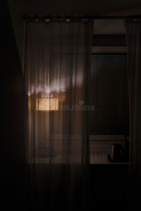 Een schemerige lamp achter een transparant gordijn op een vensterbank stock foto's