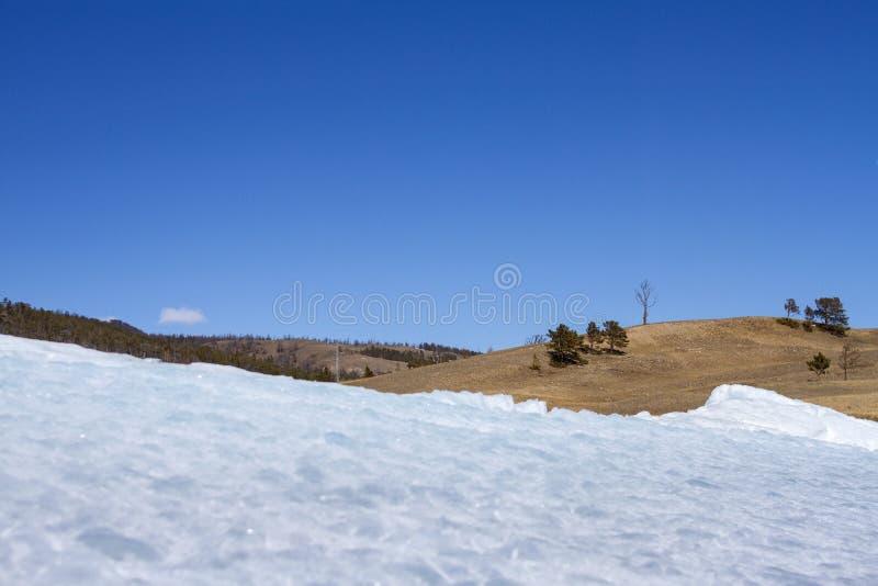 Een schilderachtig landschap met ijs op de kust van Meer Baikal op het Olkhon-eiland in de winter op een berg en hemelachtergrond stock foto