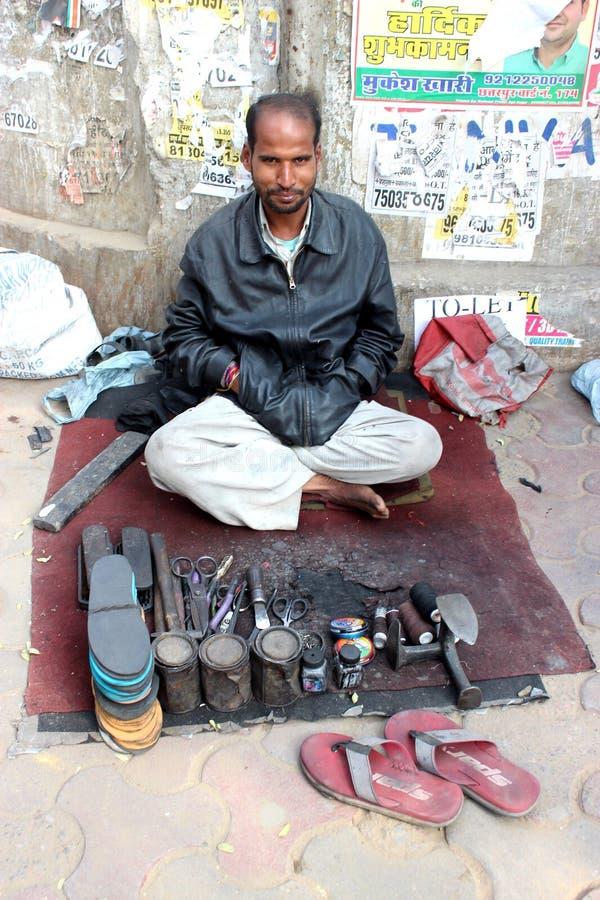 Een schoenmaker in New Delhi, India stock afbeeldingen