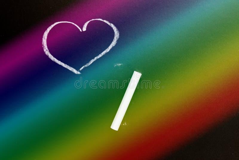 Een schoolbord met het getrokken hart Regenboog Achtergrondtextuur met exemplaarruimte stock afbeeldingen