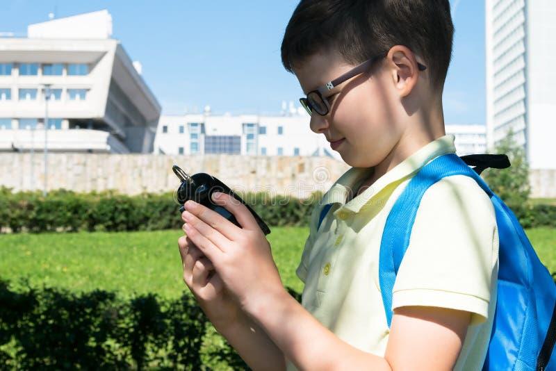 Een schooljongen in het park bekijkt de wekker, die aantoont dat de tijd leert stock afbeeldingen