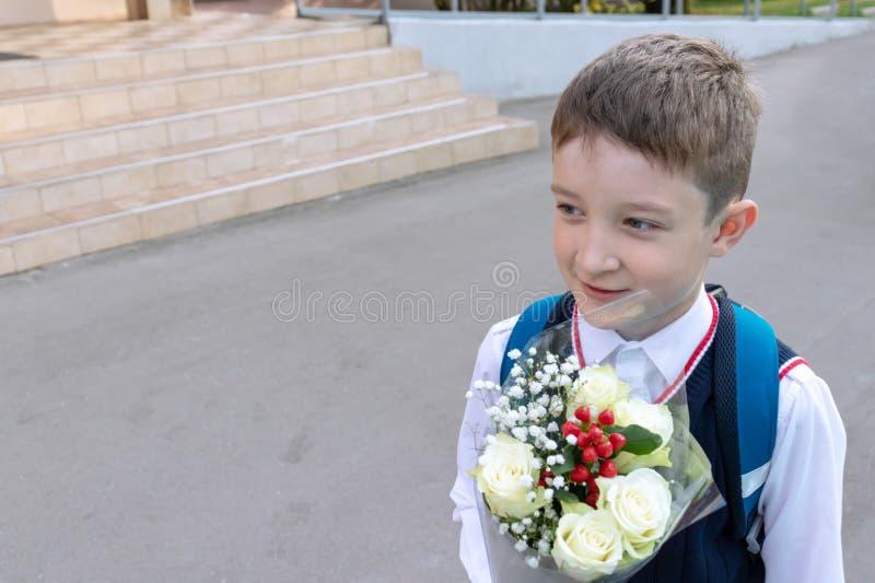 Een schooljongen met een boeket van witte rozen in zijn hand openlucht royalty-vrije stock foto