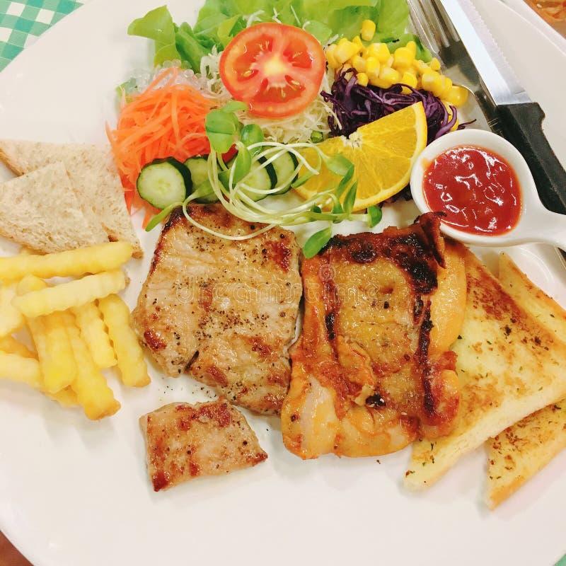 Een schotel van in brand gestoken varkensvlees en kippenlapje vlees met brood, Franse gebraden en salade royalty-vrije stock foto