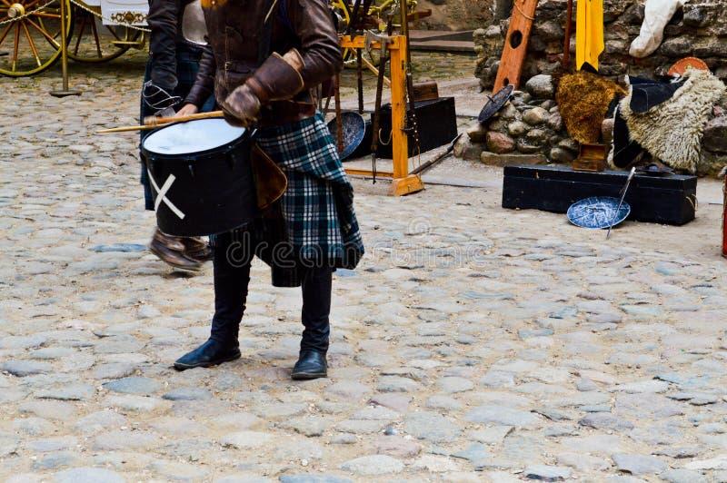 Een Schotse strijder, militair, musicus in traditioneel kostuum met een rok slaat de trommel op het vierkant van een middeleeuws  royalty-vrije stock afbeeldingen