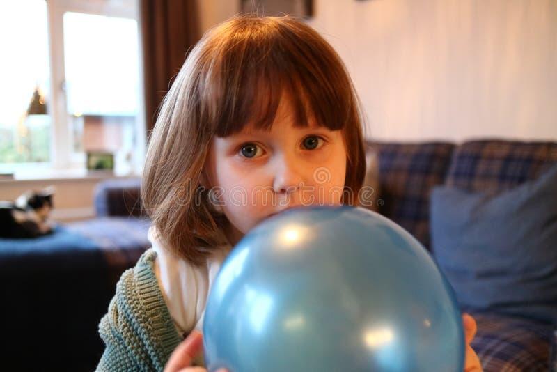 Een schuw jong meisje die achter een ballon verbergen stock foto's