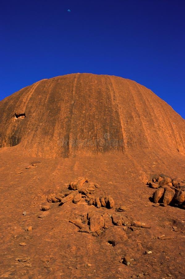Een sectie van de rotsvorming van de Rots van Uluru Ayers bij zonsopgang, de maan op de achtergrond, het Nationale Park van uluru stock afbeeldingen