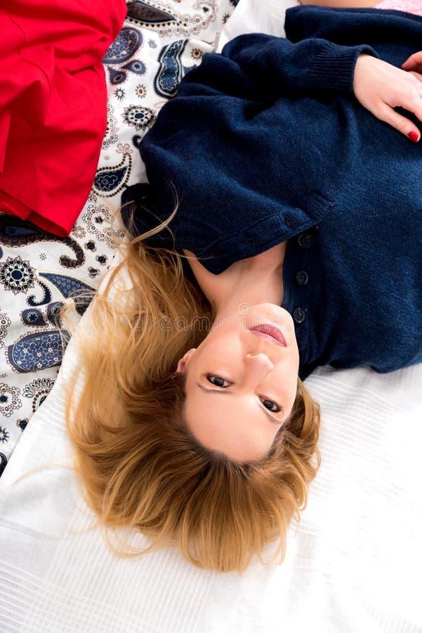 Een serieuze jonge vrouw die op een bed ligt in een sweater royalty-vrije stock afbeeldingen