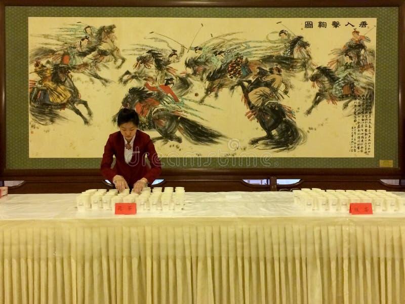 Een serveerster treft voorbereidingen om thee in de Grote Zaal van Mensen in Peking te dienen stock foto