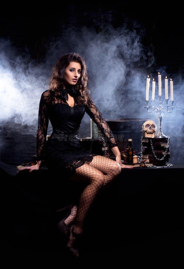 Een sexy brunette in erotische kleren met een schedel royalty-vrije stock afbeelding