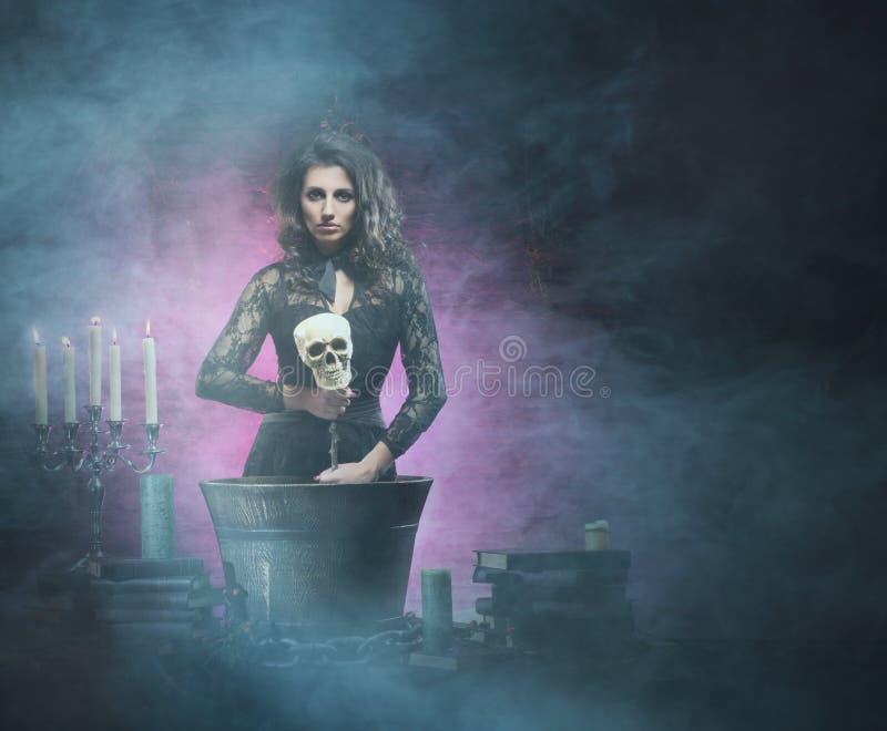 Een sexy donkerbruine heks die vergift in de kerker maken stock afbeeldingen