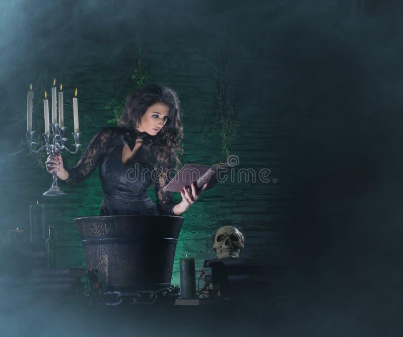 Een sexy donkerbruine heks die vergift in de kerker maken stock foto's