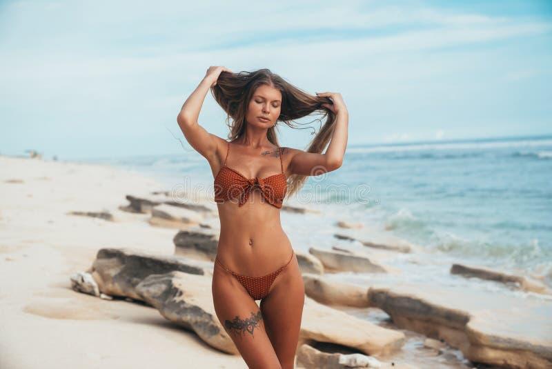 Een sexy gelooid getatoeeerd model met een vlotte huid en het zachte gezicht stellen op de kust De windspelen met het meisje ` s stock afbeelding