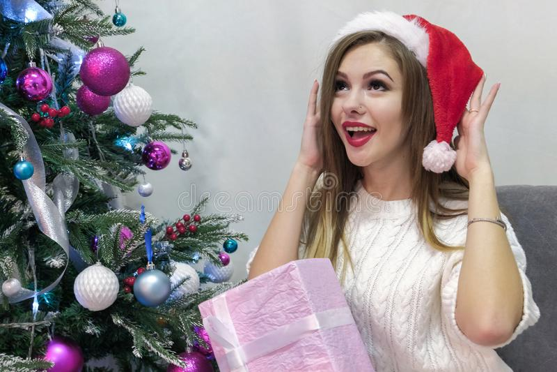 Een sexy glimlachend Europees meisjesblonde in een witte sweater en een rood GLB kijkt gelukkig omhoog in verrassing naast de Nie stock foto