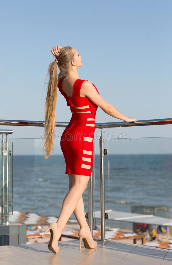 Een sexy jong meisje met lang haar op een hotelterras op een natuurlijke blauwe achtergrond De schitterende dame op het overzees  stock fotografie