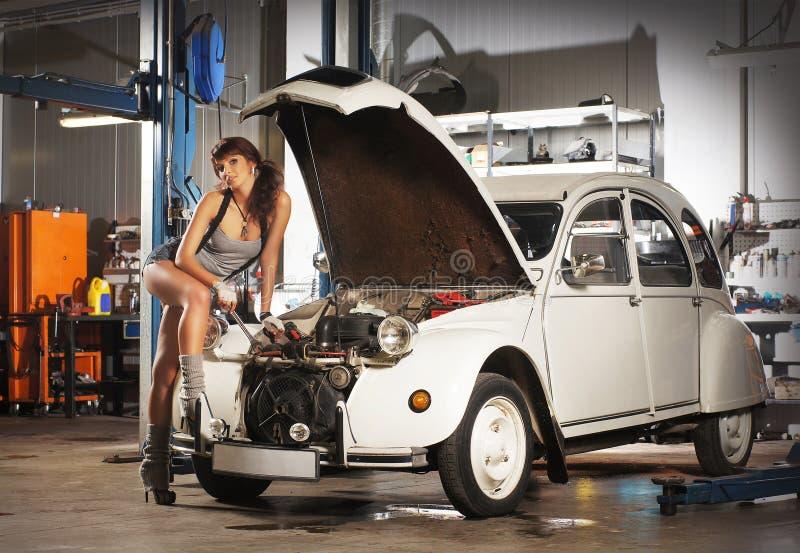 Een sexy vrouw die een retro auto in een garage herstellen for Garage auto st genest lerpt