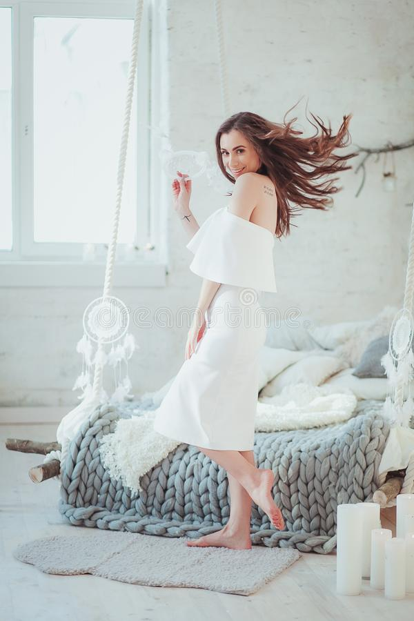 Een sexy vrouw die zich bij bed met dreamcatcher, zolder minimalistic binnenland bevinden stock afbeelding