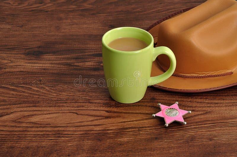 Een sheriffkenteken met een bruine cowboyhoed en een mok koffie royalty-vrije stock afbeeldingen