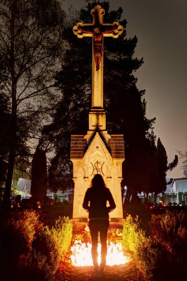 Een silhouet van een jonge vrouw voor een historisch standbeeld met een Jesus op een kruis bij Vitkovice-begraafplaats in Ostrava stock afbeelding