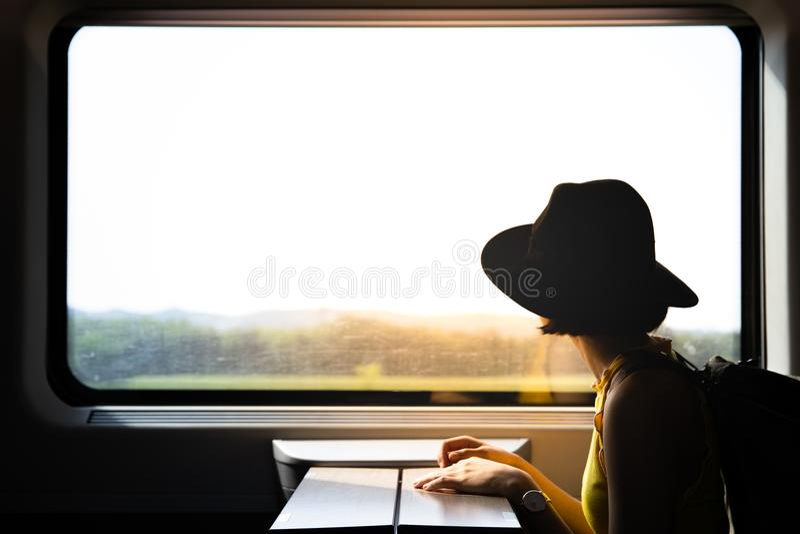 Een silhouet van het mooie hipster Aziatische vrouw reizen op de trein stock foto's