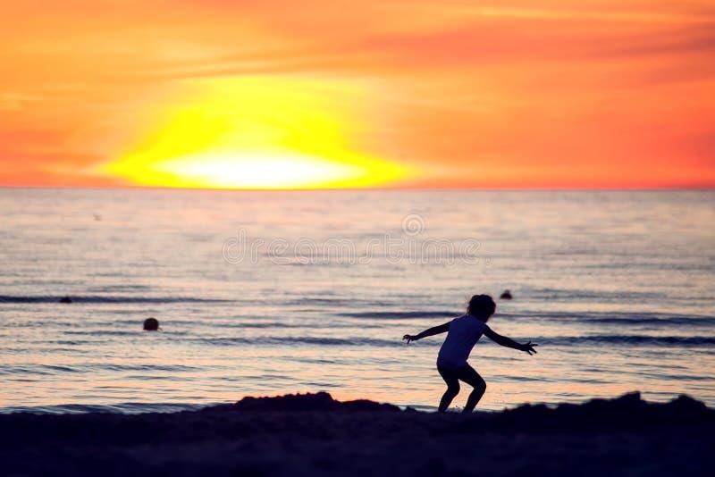 Een silhouet van een kind op het strand op zonsondergang Kinderen, de zomer en vakantieconcept royalty-vrije stock fotografie