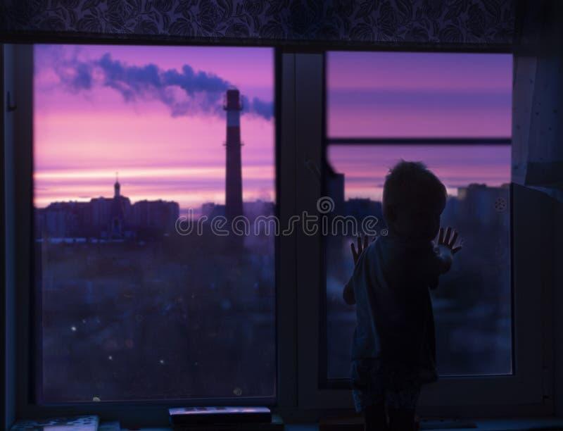 Een silhouet van een kindpeuter bij het venster bekijkt de roze dageraad en ziet rook en stedelijke huizen stock foto